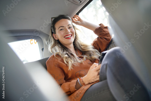 Fotomural Attractive young woman smiling at camera sitting in back of taxi