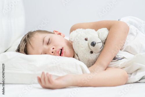 Foto  Little boy with toy bear is sleeping with his mouth open, snoring