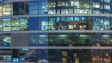 Glowing Windows In Multistory Modern Glass And Metal Office Building Light Up At Night Timelapse.
