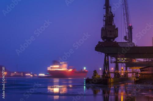 Foto op Plexiglas Poort SEAPORT AT DAWN - The cargo ship maneuvers to transhipment wharf in Swinoujscie