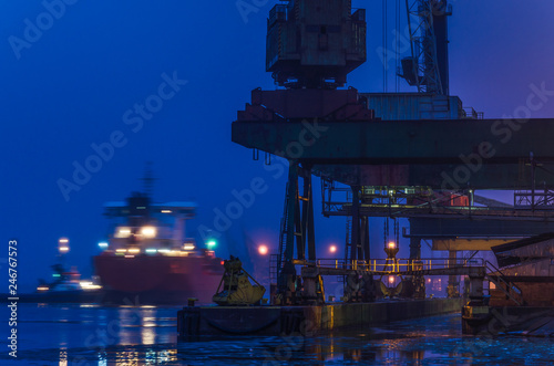 Foto op Plexiglas Poort SEAPORT AT DAWN - The cargo ship maneuvers to transhipment wharf in SwinoujscieSHIP