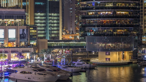 Foto  Aerial vew of Dubai Marina with shoping mall, restaurants, towers and yachts night timelapse, United Arab Emirates