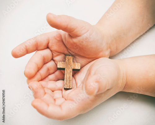 A little wooden cross in the child's hands Fototapeta