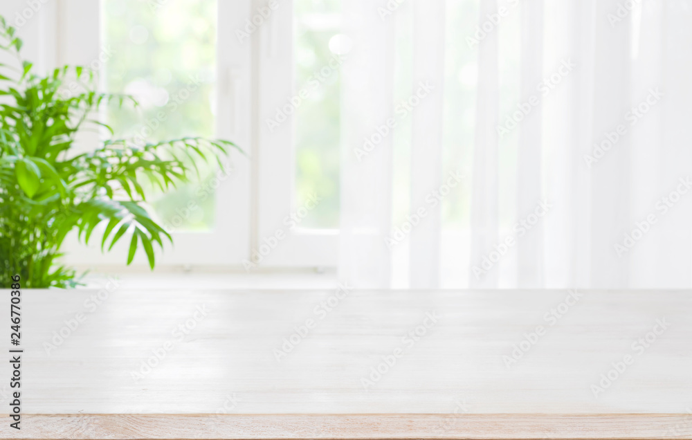 Fototapeta Wooden table top on blurred background of half curtained window