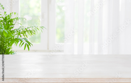 Fototapeta Wooden table top on blurred background of half curtained window obraz