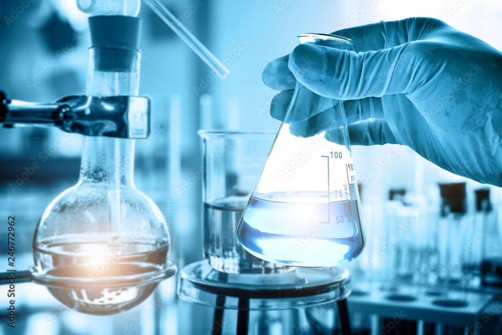 Fototapety, obrazy: hand of scientist holding flask with lab glassware in chemical laboratory background, science laboratory research and development concept