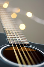 Fretboard With Strings At Black Glossy Guitar With Bokeh In The Background