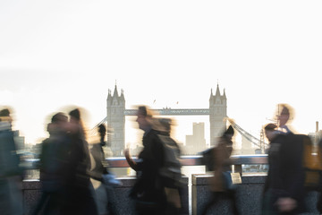 CMotion Blur Shot Of Commuters Walking To Work Across London Bridge UK With Tower Bridge In Background