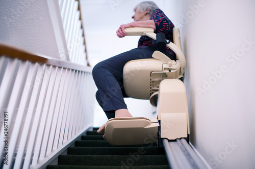 Senior Woman Sitting On Stair Lift At Home To Help Mobility Fototapeta
