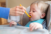 Baby Boy At Home In High Chair Being Fed Solid Food By Mother With Spoon