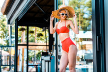 Happy Pin Up Girl Posing In Red Swimsuit, Hat And Sunglasses Near Swimming Pool
