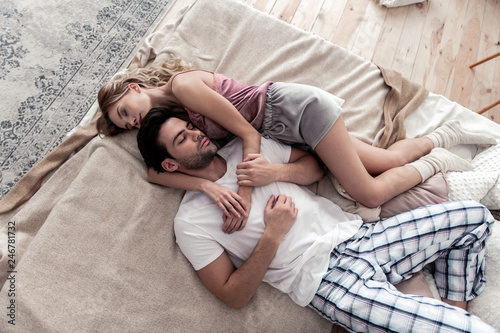Fototapeta Handsome dark-haired young man in a white shirt and his cute blond wife laying on the bed obraz na płótnie
