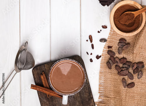 Papiers peints Pays d Afrique Hot chocolate in the cup, cocoa beans and powder on the white wooden table
