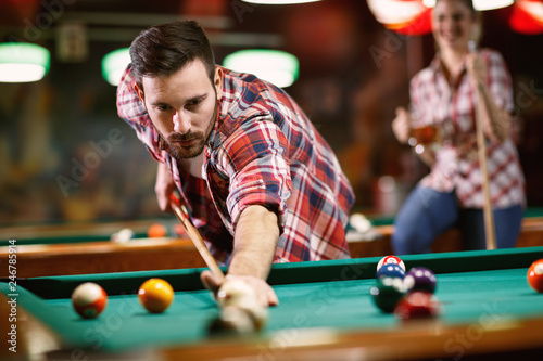 Young man playing billiard in club . Tablou Canvas