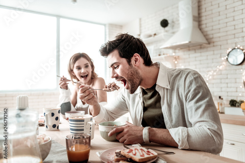 Fotografija  Bearded handsome positive man in a white shirt eating salad for breakfast