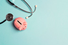 Piggy Bank With Stethoscope On Blue Background. Top View With Copy Space.