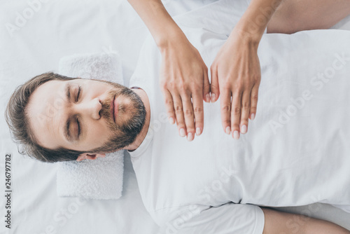 top view of bearded man with closed eyes receiving reiki treatment Canvas Print