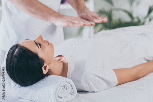 young woman lying on massage table and receiving reiki treatment Canvas Print