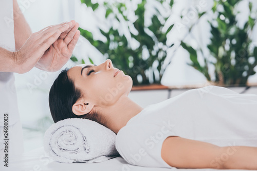 Photo  cropped shot of calm young woman with closed eyes receiving reiki treatment