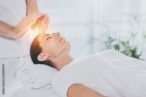 Photo  cropped shot of young woman receiving reiki therapy above head