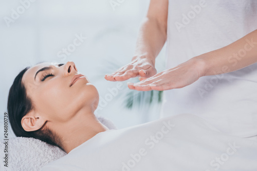 Foto cropped shot of peaceful young woman with closed eyes receiving healing treatmen