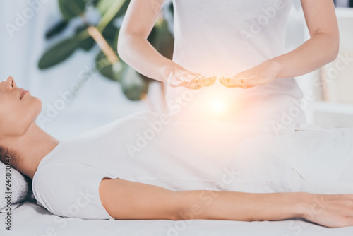 cropped shot of calm young woman receiving reiki treatment on stomach Canvas Print