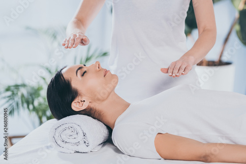 Photo  cropped shot of calm young woman receiving reiki healing therapy on head and che