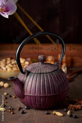Fotografia  Oriental cast iron tea pot, pistachios, orchid flowers and decorative spices