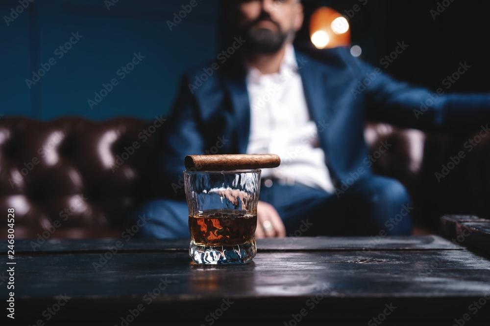 Fototapety, obrazy: Glass of brandy and cuban cigar on an old wooden table.