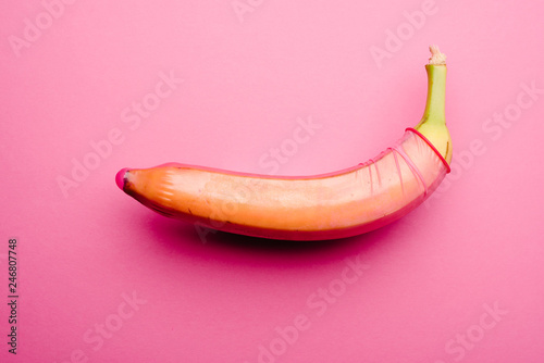 Foto op Canvas Akt Pink condom on fresh banana in front of pink background