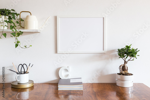 Desk with blank picture frame or poster, desk objects, office supplies, books and bonsai tree on a white background..