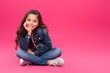 canvas print picture - adorable happy child in denim clothes sitting with hand on chin and smiling at camera on pink