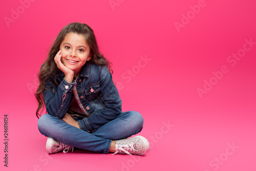 adorable happy child in denim clothes sitting with hand on chin and smiling at c Tapéta, Fotótapéta