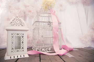 decor of the interior. Decorative white bird cage, candlestick. Decorated with flowers and pink ribbon
