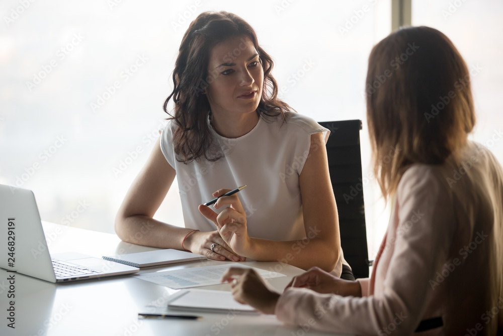 Fototapeta Two diverse serious businesswomen discussing business project working together in office, serious female advisor and client talking at meeting, focused executive colleagues brainstorm sharing ideas