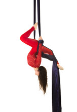 A Young Girl With Long Hair In A Red Suit Performs Gymnastic And Circus Exercises On Silk.