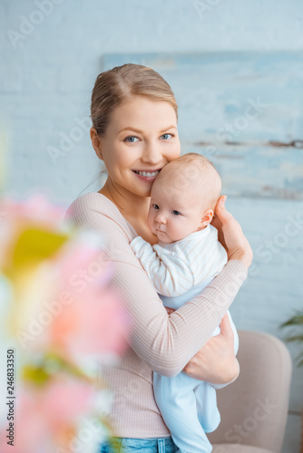 Obraz selective focus of happy young mother hugging adorable baby and smiling at camera - fototapety do salonu