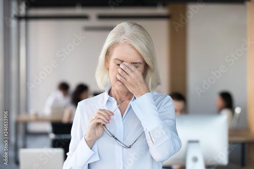 Fotografie, Obraz  Tired fatigued senior female employee taking off glasses massaging nose bridge f