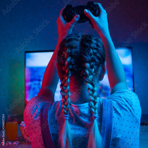 Fotografía  Gamer or streamer girl at home in a dark room with a gamepad, playing with friends online in video games