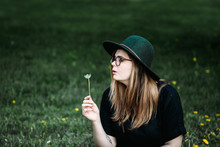 Young Woman With Hat Blowing D...