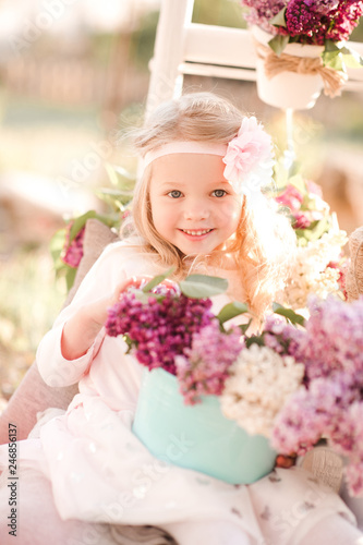 Fotografiet  Smiling baby girl 3-4 year old holding flowers outdoors