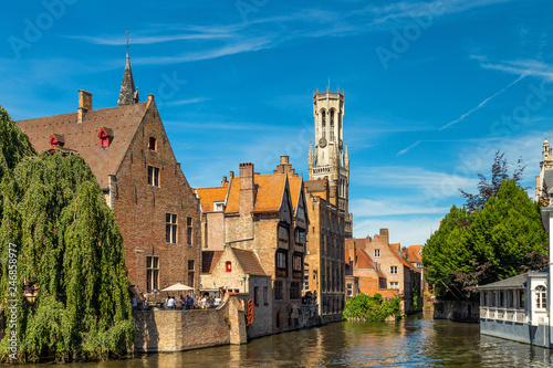 Montage in der Fensternische Brugge The Rozenhoedkaai canal in Bruges with the belfry in the background. Typical view of Bruges (Brugge), Belgium with red brick houses with triangle shaped roofs and canals.