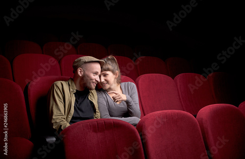 Foto auf Leinwand Akt Young cute couple sitting alone at red movie theatre and having fun