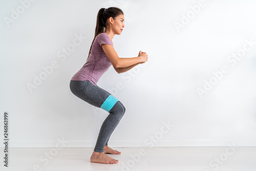 Fotografía  Resistance band fitness woman doing squat exercise with fabric booty band stretching strap