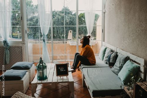 .Young beautiful woman working from home, happy and relaxed on a rainy autumn da Wallpaper Mural