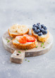 Fresh healthy mini sandwiches with cream cheese, fruits and berries on vintage wooden board. Strawberries, blueberries, bananas and raspberries on stone kitchen table background.Top view.
