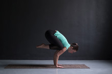 Young Woman Practicing Yoga, Doing Crane Exercise, Bakasana Pose, Working Out.