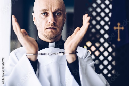 Fotografia Catholic priest in handcuffs in church.