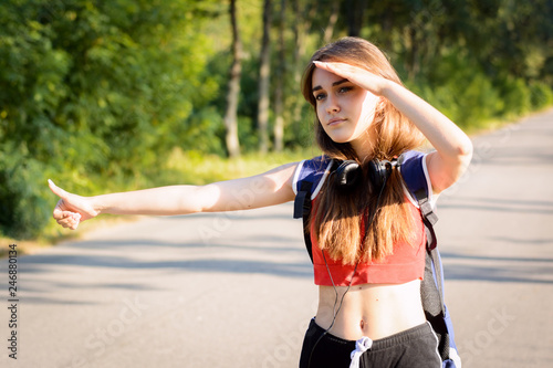 Exhausted girl standing at the scorching summer sun looking