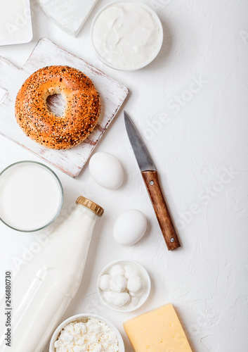 Fresh dairy products on white table background. Glass of milk, bowl of flour and cottage cheese and eggs. Fresh baked bagel with knife. Steel whisk. Top view